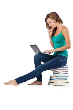 Student with netbook sitting on books photo