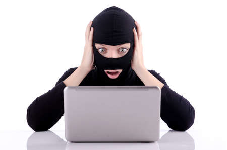 Hacker with computer wearing balaclava Stock Photo - 18663534