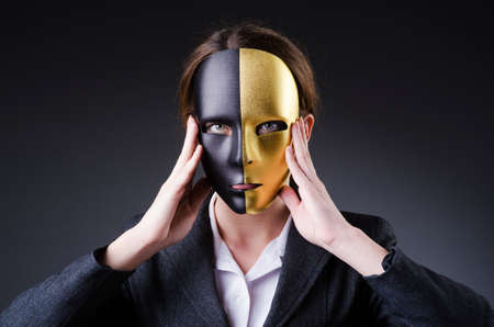 Woman with mask in hypocrisy concept photo