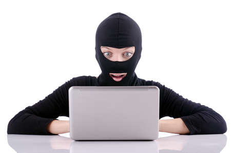 Hacker with computer wearing balaclava Stock Photo - 18664496