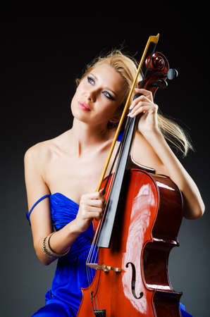 Attractive woman with cello in studio photo