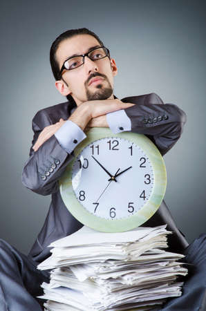 Man with clock and pile of papers Stock Photo - 18651334
