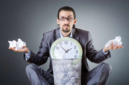 Man with clock and pile of papers photo