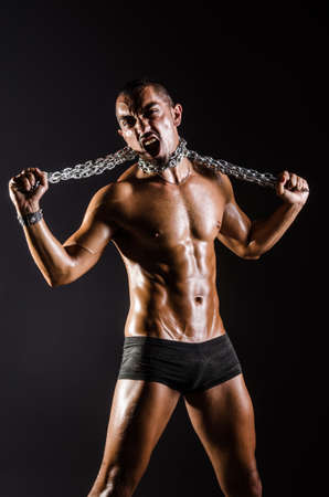 Muscular man with chain on black background photo