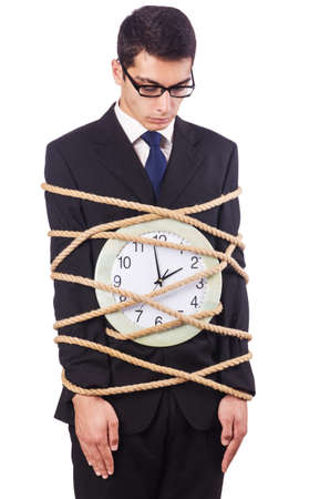 time bound: Businessman tied to clock on white