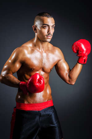 Boxer with red gloves in dark room photo