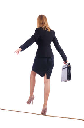 Businesswoman walking on tight rope isolated photo