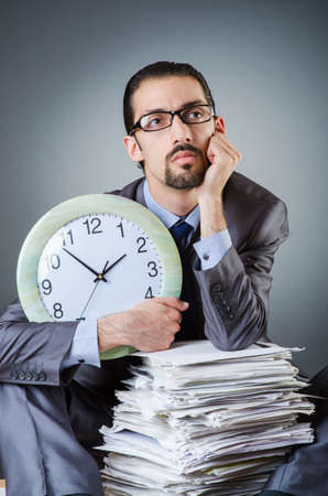 Man with clock and pile of papers Stock Photo - 19029197
