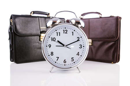 Alarm clock and briefcase isolated on white photo