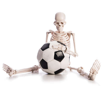 Skeleton with football isolated on the white photo