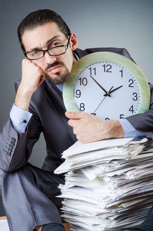 Man with clock and pile of papers Stock Photo - 20258493