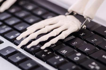 overworking: Skeleton working on the keyboard
