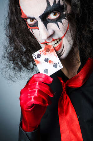 harlequin clown in disguise: Evil clown with cards in dark room
