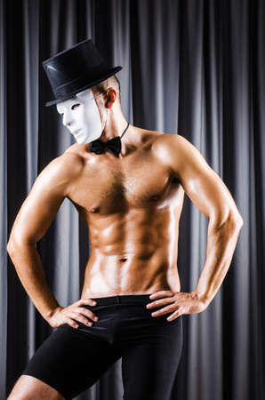 Muscular actor with mask against curtain Stock Photo - 19292574