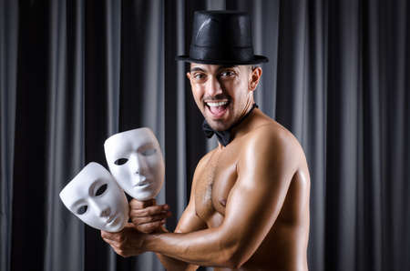 Muscular actor with mask against curtain photo