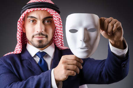 Arab with masks in dark studio photo