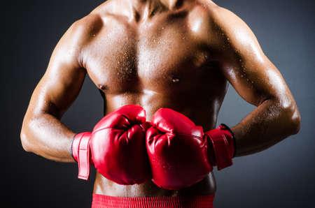 boxeador: Boxeador con los guantes rojos en cuarto oscuro Foto de archivo