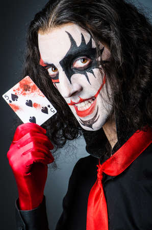 Evil clown with cards in dark room photo
