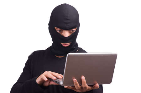 Hacker with computer wearing balaclava photo