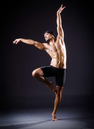 male ballet dancer: Dancer dancing in the dark studio Stock Photo