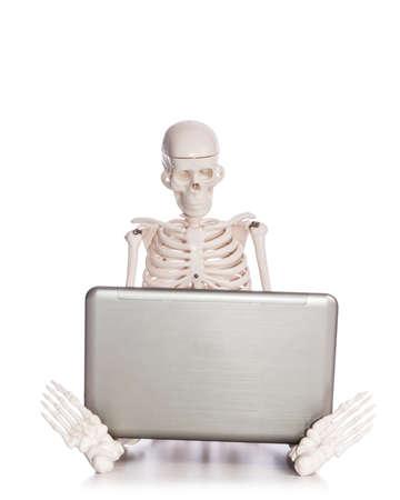 overworking: Skeleton working on laptop Stock Photo