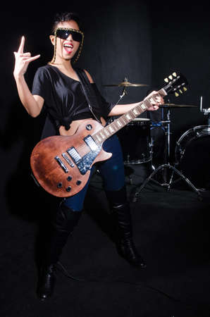 Woman guitar player during concert photo