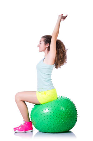 Young woman with ball exercising on white photo