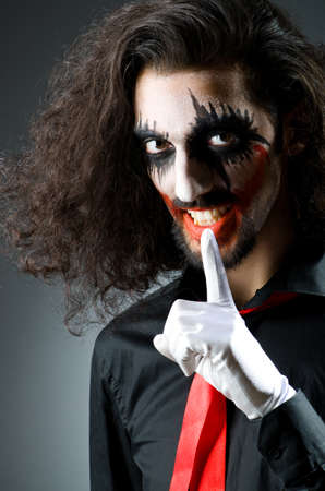 harlequin clown in disguise: Joker personification with man in dark room