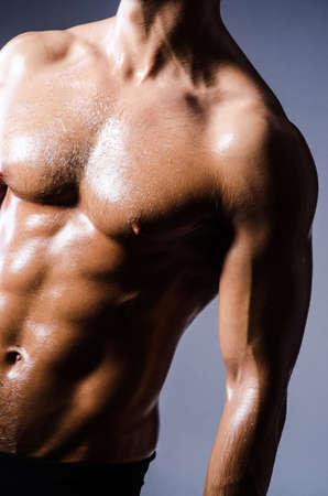 nudo maschile: Uomo muscolare in studio scuro