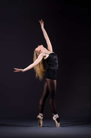Ballerina dancing in the dark studio Stock Photo - 20101606