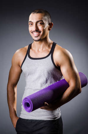 Muscular man with mat in studio photo