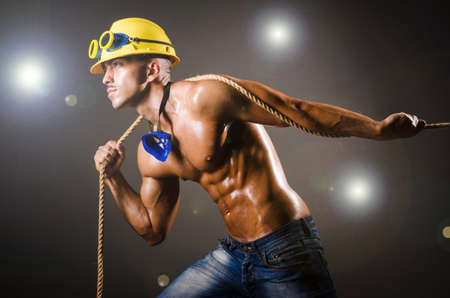 builder pulling rope in darkness photo