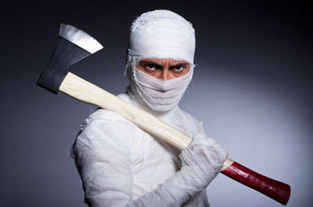 Mummy with axe in halloween concept photo