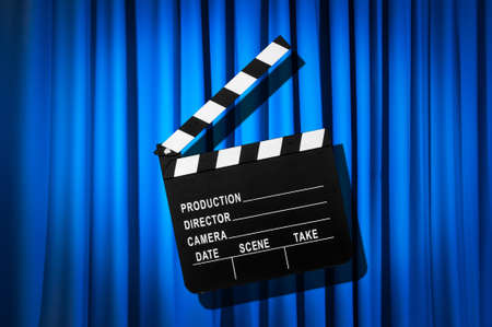 Movie clapper board against curtain photo