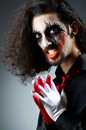 Joker personification with man in dark room photo