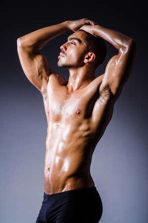 desnudo masculino: Hombre muscular en el estudio oscuro
