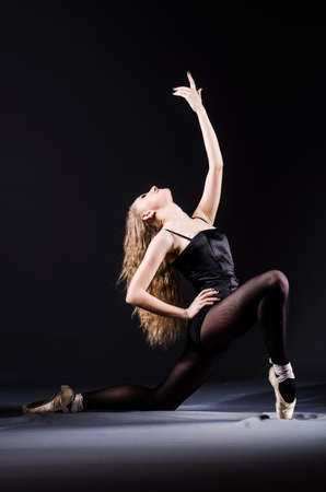 Ballerina dancing in the dark studio photo