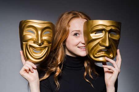 Redhead vrouw iwith maskers in hypocrisie consept tegen grijze achtergrond