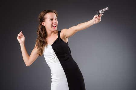Woman with gun against dark background Stock Photo - 30442425