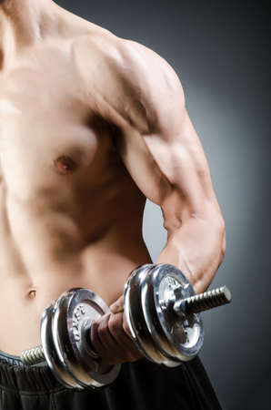Muscular ripped bodybuilder with dumbbells photo