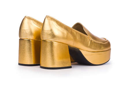 Golden woman shoes isolated on the white photo
