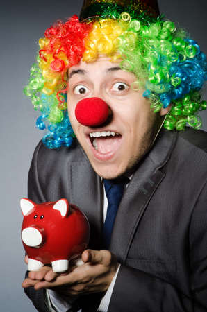 Clown with piggybank in funny concept photo