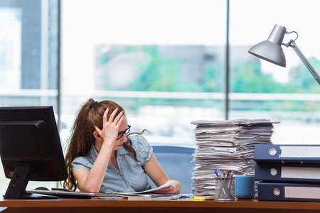 Stressed businesswoman with stack of papers Banco de Imagens