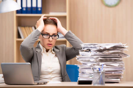 Businesswoman under stress from too much work in the office Stockfoto