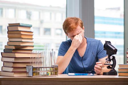 Jonge student moe en uitgeput voorbereiding voor scheikunde examen Stockfoto