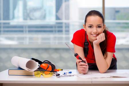 Jeune femme en salopettes faisant des réparations Banque d'images - 66766419