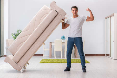 Man moving furniture at home Stock Photo