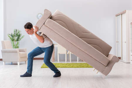 Man moving furniture at home Banque d'images