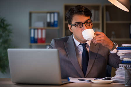 Businessman staying in the office for long hours Stock Photo