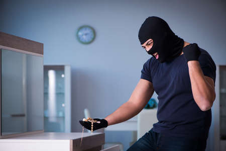 Robber wearing balaclava stealing valuable things Stock Photo